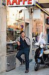 Mid adult man sitting at sidewalk cafe