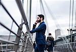 Businessman standing on footbridge talking on smartphone, London, UK