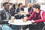 Friends at sidewalk cafe enjoying a coffee chatting