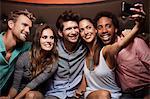 Happy friends taking self portrait at nightclub
