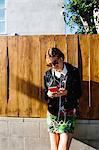 Young woman outdoors, using smartphone, wearing earphones