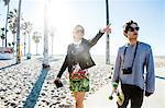 Young couple walking along beach walkway, young woman pointing