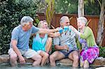 Group of seniors toasting at pool