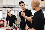 Auto mechanic teacher explaining metallic rod to students in training class