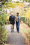 Full length of happy senior man with caretaker walking in park