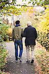 Full length rear view of senior man with caretaker walking in park
