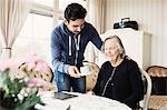 Caretaker serving coffee to senior woman sitting at nursing home