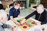 Caretaker playing Ludo with seniors at nursing home