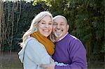 Mature couple hugging, looking at camera smiling