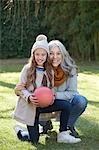 Grandmother and granddaughter holding football looking at camera smiling