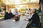 Happy senior couples discussing at outdoor restaurant