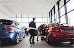 Senior man and woman examining car at showroom