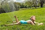Young girl lying under garden sprinkler in field