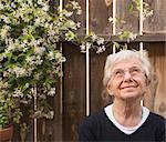 Portrait of smiling senior woman in garden gazing upward