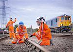 Apprentice railway worker instructed by engineer on railway
