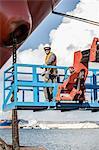Portrait of worker on viewing platform inspecting oil tanker