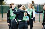 Female netball team celebrating on netball court