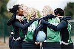 Female netball team celebrating in huddle on netball court