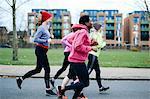 Five female runners running along city sidewalk