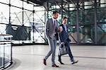 Corporate businessmen walking in modern lobby
