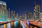 Dubai Marina at night with light trails of boats on the water, long term exposure, Dubai, UAE