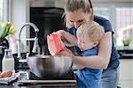 Mother helping son bake cake