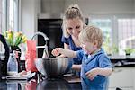 Mother helping son bake cake, son cracking egg