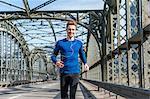 Young man exercising, running on bridge