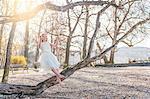 Woman wearing chiffon dress swinging on tree swing smiling