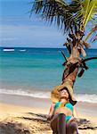 Young woman wearing bikini sunbathing on palm tree at beach, Dominican Republic, The Caribbean