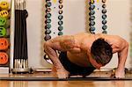 Tattooed man exercising on yoga mat in gym