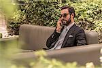 Businessman talking on smartphone on hotel garden sofa, Dubai, United Arab Emirates