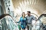 Tourist couple moving up shopping mall escalator, Dubai, United Arab Emirates