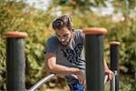 Young man using park exercise equipment, Dubai, United Arab Emirates