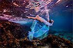 Woman underwater in ocean over coral reef