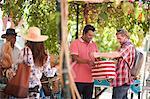 Market trader selling tote bag to tourist