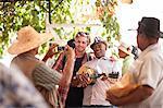 Market trader taking photograph of tourist posing with market trader playing ukulele