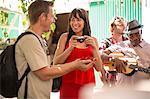 Tourists standing beside market trader playing ukulele
