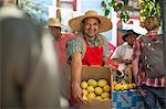 Market trader enticing shoppers to buy lemon