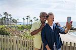 Senior couple outdoors, taking self portrait, using smartphone