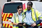 Ambulancemen writing on clipboard