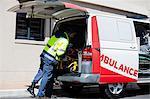 Ambulance men bringing injured people inside ambulance car