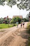 Sweden, Smaland, Vastervik, Hummelstad, Rear view of children (6-7, 10-11, 12-13) walking along village road