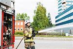 Sweden, Sodermanland, Sodertalje, Female firefighter using fire hose next to truck