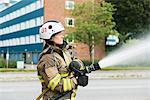 Sweden, Sodermanland, Sodertalje, Female firefighter using fire hose in street
