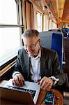 Sweden, Businessman using laptop on train