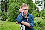 Sweden, Ostergotland, Vikbolandet, Portrait of man sitting on chair in backyard