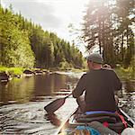 Sweden, Vastmanland, Svartalven, Man paddling canoe along river