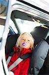 Sweden, Little blonde boy (2-3) fastened to seat in car