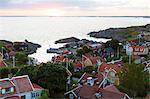 Sweden, Stockholm Archipelago, Sodermanland, Landsort, Oja, Townscape with cottages next to sea at sunset